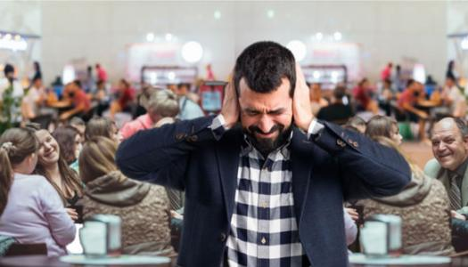 man covering his ears in noisy restaurant